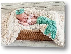 Улыбающийся новорожденный мальчик в сером костюме кролика
