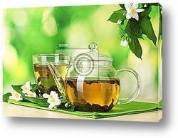 Стеклянный чайник и чашка с экзотическим зеленым чаем