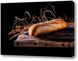 Постер Контрастный снимок французского багета на фоне деревянной столешницы в стиле минимализм.