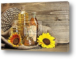 Постер Oil in bottles, sunflowers and seeds, on wooden background