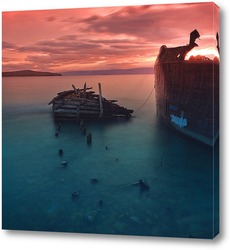 Солнце всходит между двумя скалами братьями близнецами, которые возвышаются над морской рябью