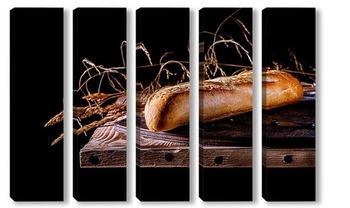 Модульная картина Контрастный снимок французского багета на фоне деревянной столешницы в стиле минимализм.